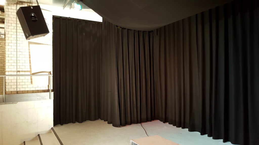 Blick auf den linken Bühnenbereich. Dahinter befinden sich u.a. die Schalt- und Steuereinheit (Strom, Mikrophonanschluss, Technikerzugang)