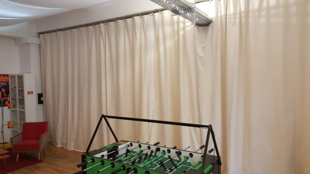 Die Lounge wirkt sehr freundlich, warm und gemütlich. Außerdem absorbiert der Kalmuck-Akustikvorhang den Großteil an Schall, Hall und Nachhall, der durch den Kicker-Ball entsteht und nach außen (in umliegende Büroräume) drang.